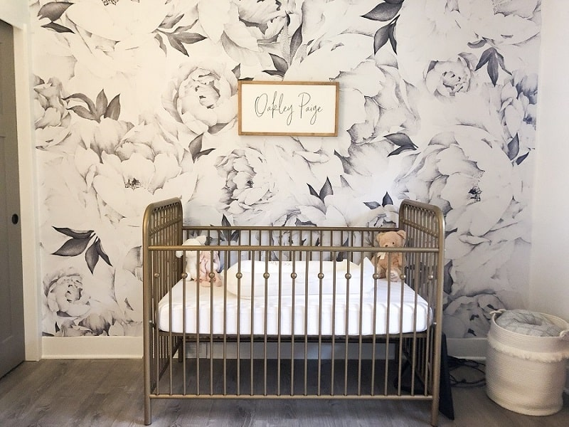 Wood framed name sign on gray floral wallpaper wall in baby girl nursery. Gold crib accent.
