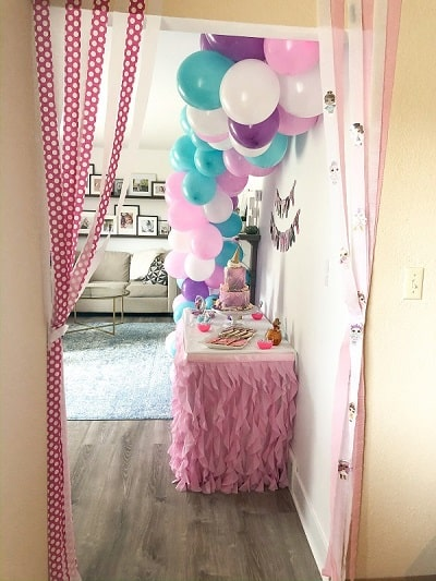 LOL Surprise Birthday Party cake table with balloon garland and streamers