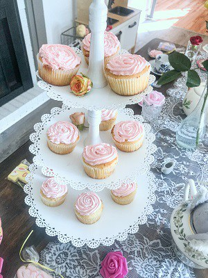 3-tier stand of vanilla cupcakes with pink whipped cream frosting.
